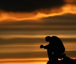 Prayer in a dark sunset