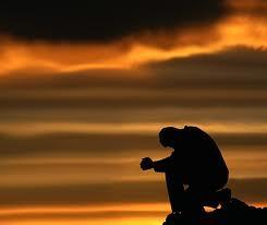 Prayer in a dark sunset
