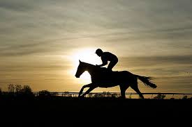 MAN RIDING HORSE IN THE SUNSET